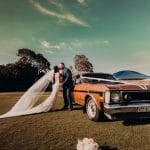 Bride and Groom at Sandstone Point Hotel with a Vintage Car